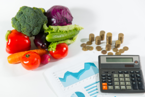 Vegetables, money, and calculator on table