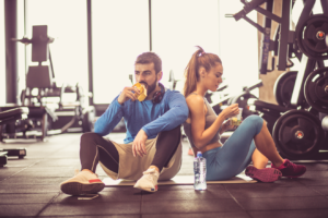 Man and woman eating in gym